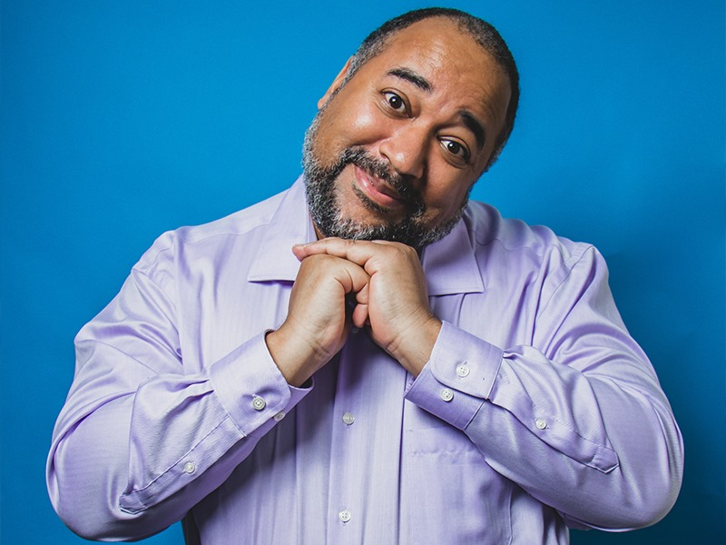 The Velvet Duke. A Black man with a beard, purple shirt and blue background, clutching his hands in a sweet way under his chin.